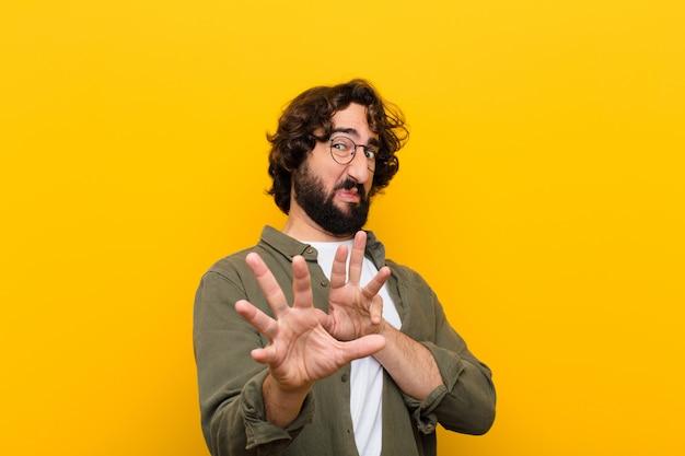 Jeune homme fou se sentant dégoûté et nauséeux, s'éloignant de quelque chose de méchant, puant ou puant, disant beurk contre un mur jaune Photo Premium