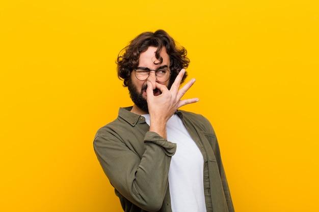 Jeune homme fou se sentant dégoûté, tenant son nez pour éviter de sentir une puanteur fétide et déplaisante Photo Premium