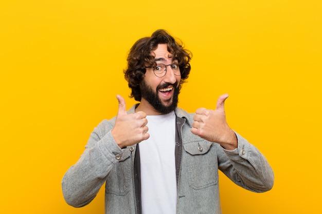 Jeune homme fou souriant regardant largement heureux positif positif confiant et réussi avec les deux pouces Photo Premium