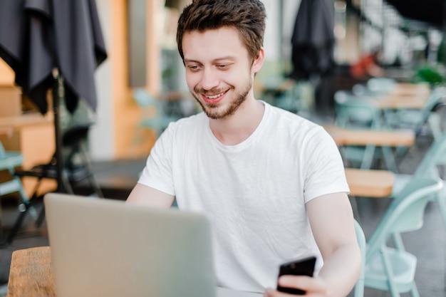 Jeune homme, freelance, travail, téléphone, ordinateur portable, café, dehors Photo Premium