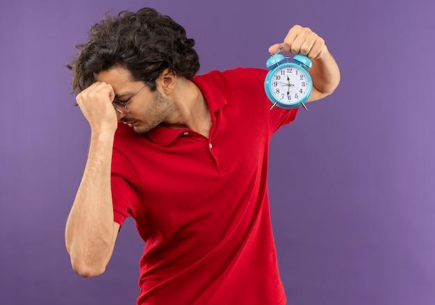 Jeune Homme Frustré En Chemise Rouge Avec Des Lunettes Optiques Détient Horloge Et Met La Main Sur Le Visage Isolé Sur Mur Violet Photo gratuit
