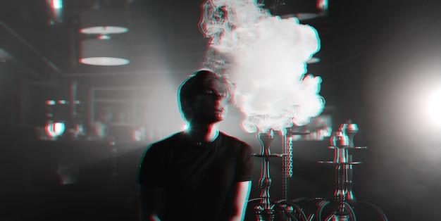 Jeune Homme Fume Un Narguilé Et Laisse échapper Un Nuage De Fumée Photo Premium
