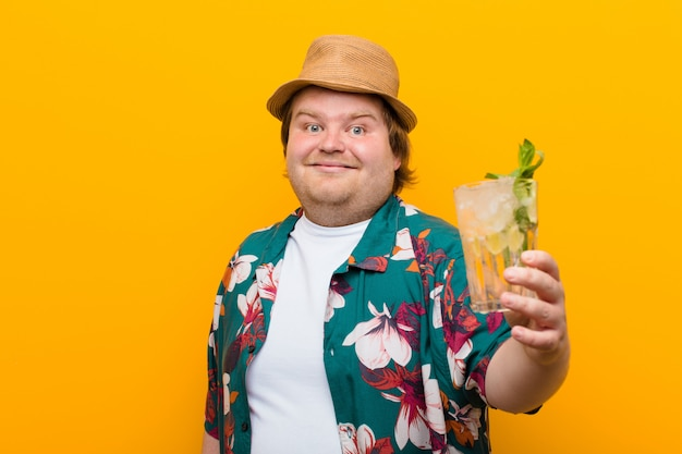 Jeune homme de grande taille avec un mur plat de boisson mojito Photo Premium