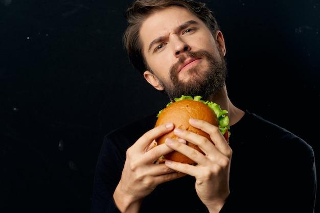 Jeune Homme Avec Un Hamburger Juteux Dans Ses Mains, Un Homme Mangeant Un Hamburger Photo Premium