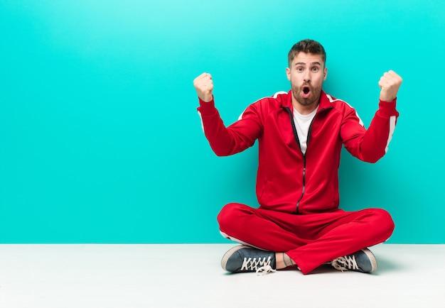 Jeune Homme Handosme Célébrant Un Succès Incroyable Comme Un Gagnant, L'air Excité Et Heureux En Disant: Prenez ça! Contre Un Mur Plat Photo Premium