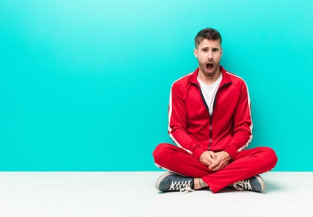 Jeune Homme Handosme Se Sentant Terrifié Et Choqué, Avec La Bouche Grande Ouverte, Surpris Contre Le Mur De Couleur Plat Photo Premium