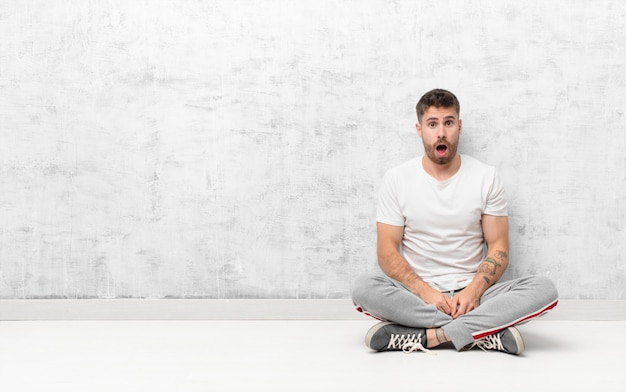 Jeune Homme Handosme à Très Choqué Ou Surpris, Regardant Avec La Bouche Ouverte En Disant Wow Contre Le Mur De Couleur Plat Photo Premium