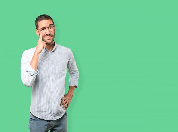 Jeune Homme Hésitant Fait Un Geste De Prudence Avec Sa Main Pointant Vers Son œil Photo Premium
