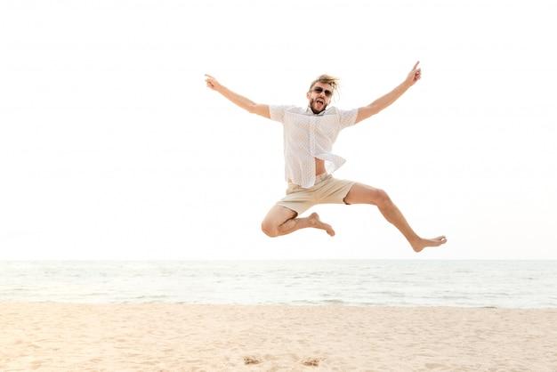 Jeune homme heureux énergique, sautant à la plage Photo Premium