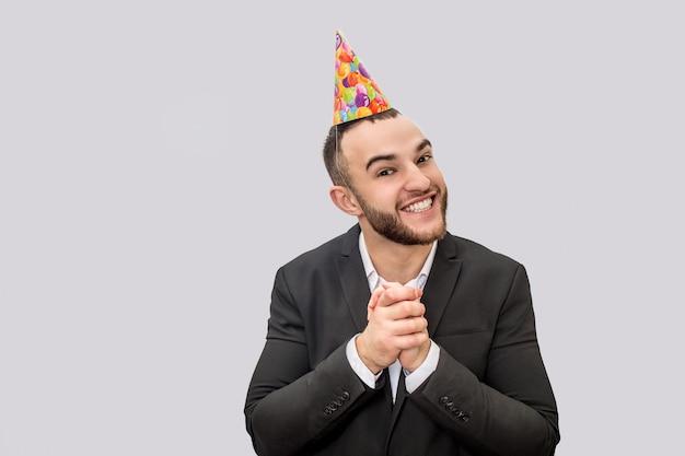 Un Jeune Homme Heureux Et Excité Garde Les Mains Ensemble. Il Regarde La Caméra Et Sourit. Guy Porte Un Cône Festif Sur La Tête. Photo Premium