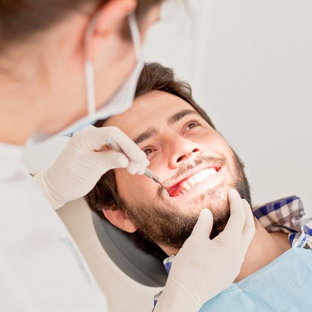 Jeune homme heureux et femme dans un examen dentaire chez dentiste Photo Premium