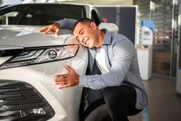 Jeune homme heureux pour sa nouvelle voiture Photo gratuit