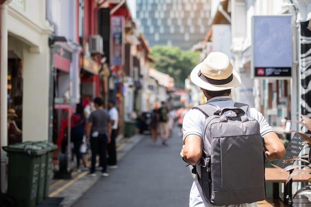 Jeune homme hipster voyageant avec un sac à dos et un chapeau Photo Premium