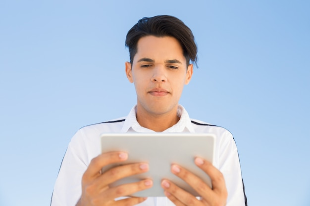 Jeune homme hispanique à l'aide d'une tablette à l'extérieur Photo gratuit