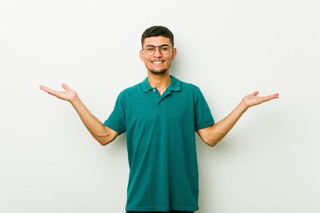 Jeune homme hispanique fait ses gammes avec les bras, se sent heureux et confiant. Photo Premium