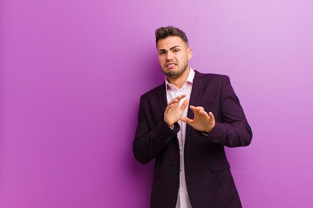 Jeune homme hispanique se sentant dégoûté et nauséeux, s'éloignant de quelque chose de méchant, puant ou puant, disant beurk Photo Premium