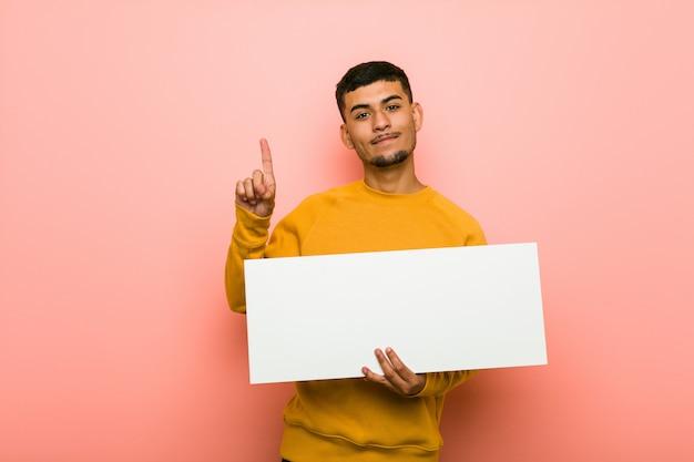 Jeune homme hispanique tenant une pancarte Photo Premium
