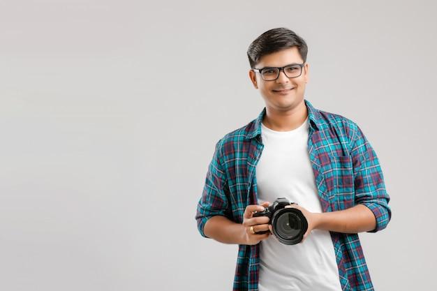 Jeune homme indien capturant une photo avec l'appareil photo Photo Premium