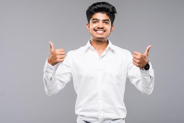 Jeune Homme Indien Debout Sur Un Mur Gris Isolé Approuvant Faire Un Geste Positif Avec La Main, Les Pouces Vers Le Haut, Souriant Et Heureux De Réussir Photo gratuit