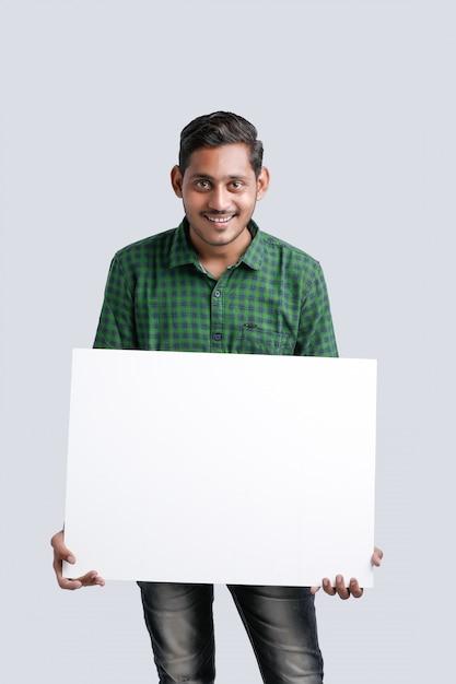 Jeune homme indien montrant vide chanter conseil sur fond blanc Photo Premium