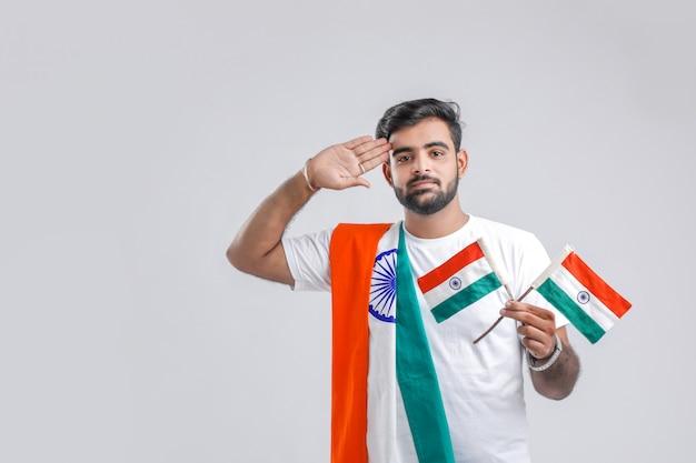 Jeune homme indien saluant drapeau indien Photo Premium