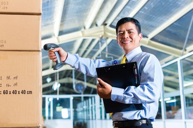 Jeune homme indonésien en entrepôt avec scanner Photo Premium