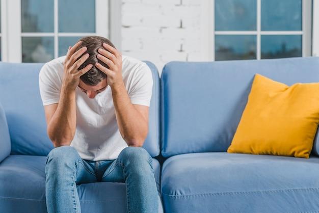 Un Jeune Homme Inquiet Assis Sur Un Canapé Bleu Souffrant De Maux De Tête Photo Premium