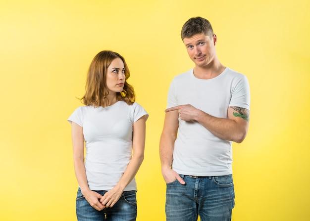 Jeune homme intelligent blâmant sa copine sur fond jaune Photo gratuit