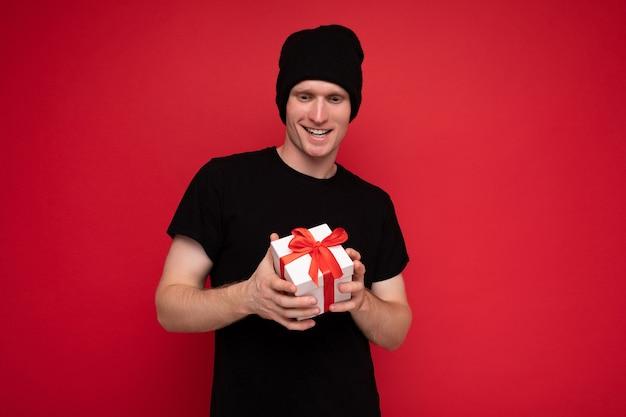 Jeune Homme Isolé Sur Mur De Fond Rouge Portant Un Chapeau Noir Et Un T-shirt Noir Tenant Une Boîte Cadeau Blanche Avec Un Ruban Rouge Et Regardant La Caméra. Photo Premium