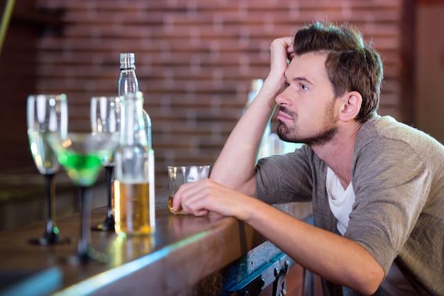 Jeune homme ivre buvant de l'alcool au bar. Photo Premium