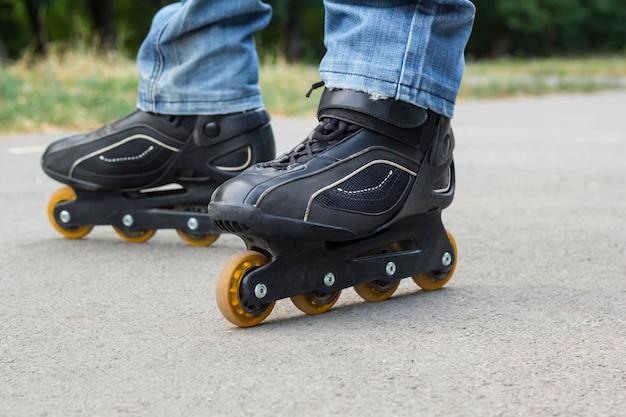 Jeune homme en jeans, équitation patins à roulettes dans la ville. bouchent les jambes Photo Premium