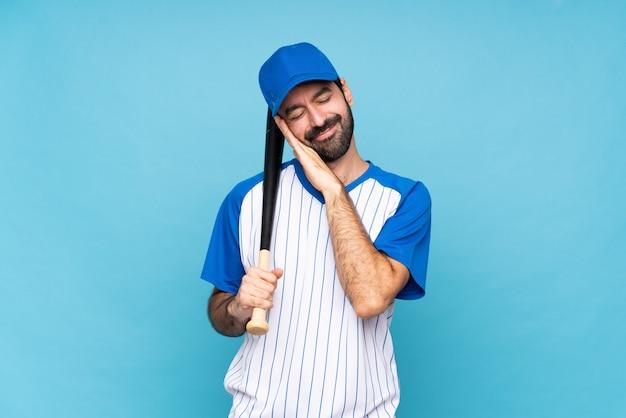 Jeune homme jouant au baseball sur fond bleu isolé, geste de sommeil en expression dorable Photo Premium