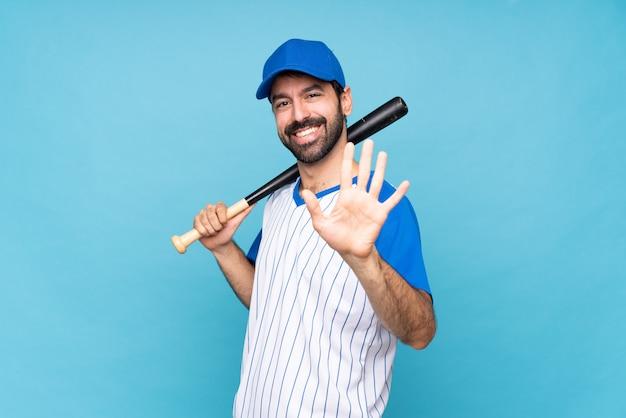 Jeune homme jouant au baseball sur mur bleu isolé comptant cinq avec les doigts Photo Premium
