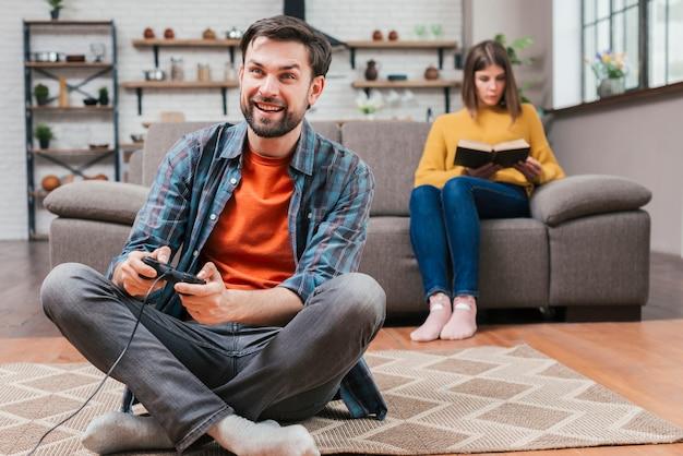 Jeune homme jouant au jeu vidéo avec joystick et sa femme assise sur un canapé en toile de fond Photo gratuit