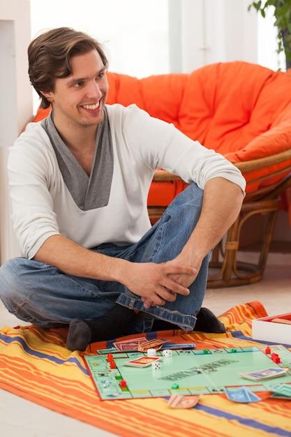 Jeune homme jouant à un jeu à la maison Photo gratuit