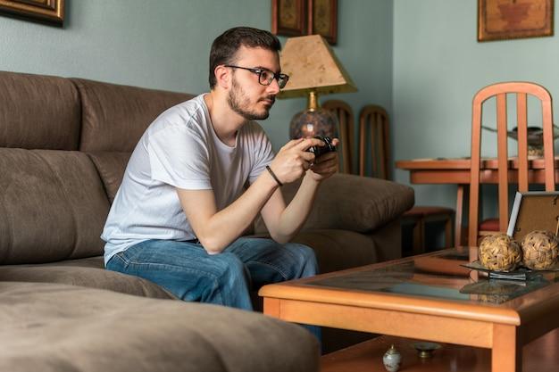 Jeune homme jouant à un jeu vidéo avec une manette sans fil Photo Premium