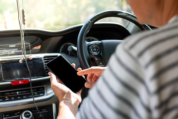 Jeune homme joue au mobile en conduisant la voiture Photo Premium