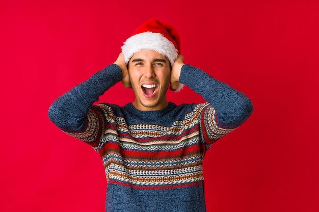 Jeune homme le jour de noël, acclamant insouciant et excité. concept de victoire. Photo Premium