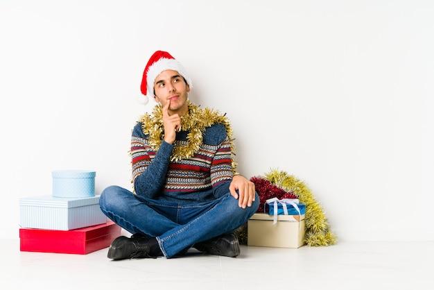 Jeune homme le jour de noël touche le ventre, sourit doucement, concept de manger et de satisfaction. Photo Premium