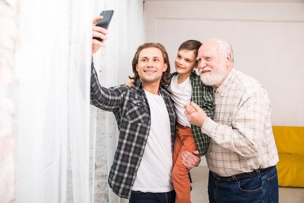 Jeune homme joyeux prenant selfie en famille Photo gratuit