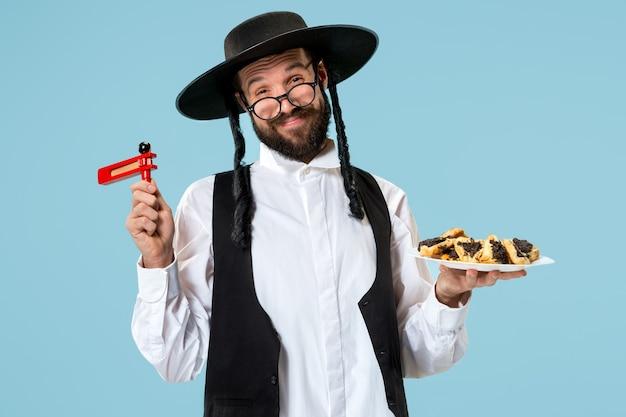 Le Jeune Homme Juif Orthodoxe Avec Des Biscuits Hamantaschen Pour Le Festival Pourim. Vacances, Célébration, Judaïsme, Pâtisserie, Tradition, Cookie, Concept De Religion Photo gratuit