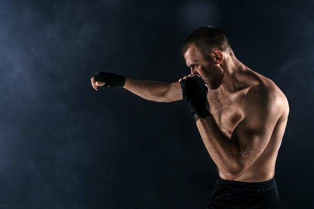 Le Jeune Homme Kickboxing Sur Fond Noir Photo gratuit