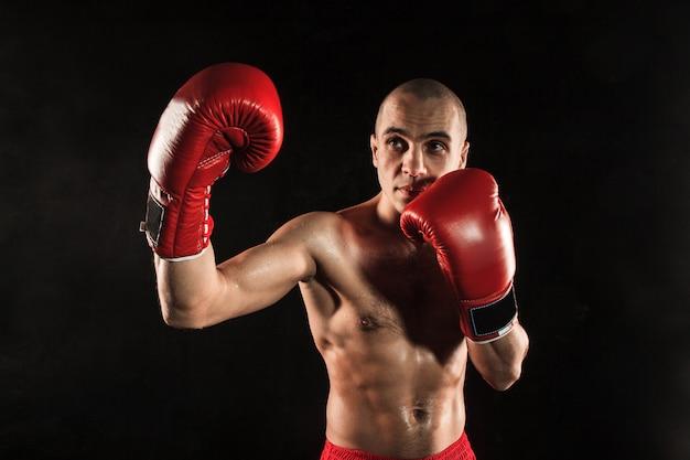 Jeune Homme Kickboxing Sur Noir Photo gratuit
