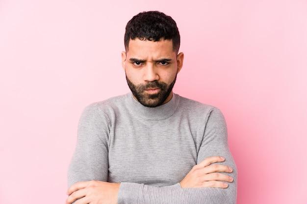 Jeune Homme Latin Contre Un Mur Rose Isolé Face Fronçant Les Sourcils De Mécontentement, Garde Les Bras Croisés. Photo Premium