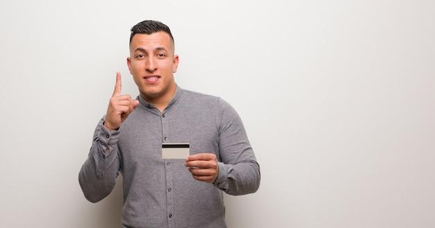 Jeune homme latin détenant une carte citant le numéro un Photo Premium