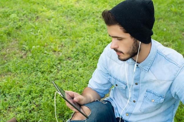 Jeune Homme Latin Avec Tablette à L'extérieur. Photo Premium