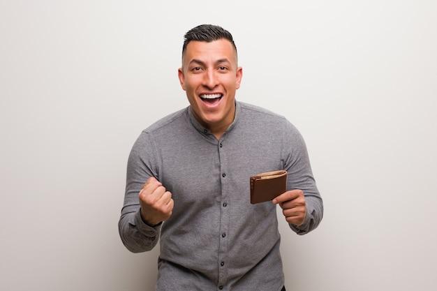 Jeune homme latin tenant un portefeuille surpris et choqué Photo Premium