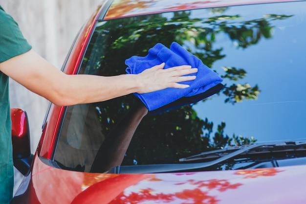 Jeune homme à laver et essuyer une voiture à l'extérieur Photo Premium