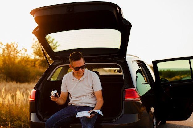 Jeune homme lisant un livre et mangeant un chocolat sur le coffre de la voiture Photo gratuit