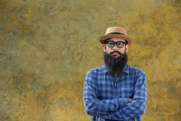 Jeune homme avec une longue barbe portant un chapeau et des lunettes Photo gratuit